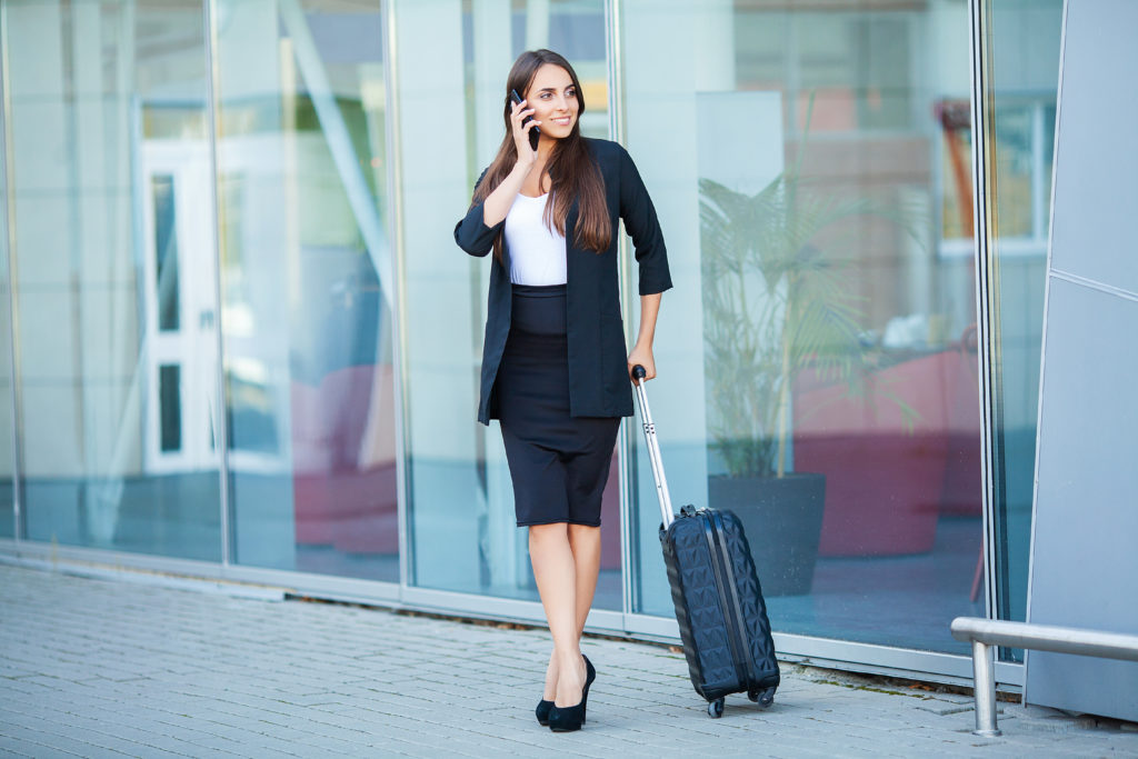 Business woman at the airport on the phone with luggage.